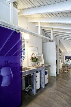 Η συρόμενη πόρτα από μοβ κρύσταλλο οδηγεί στο ντους, ενώ ο νιπτήρας από γκρίζο μάρμαρο είναι εκτεθειμένος στον ανοιχτό χώρο του σπιτιού.