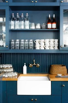 Water bottles, mugs, and votives are stored above a white apron sink at one end of the bar.