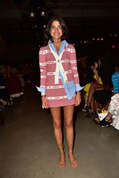 Leandra Medine wears a button-down shirt, Miu Miu striped sweater and skirt, and lace-up sandals