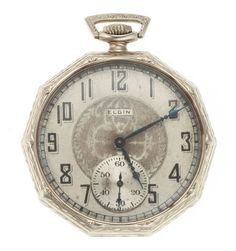 Elgin 14k Gold 17 Jewel Pocket Watch Case: 14k white gold, octagon, 12 size, engraved on the back cover, small monogram on the back cover, side swing out Dial: two-tone metal, Arabic, blue kite hands Movement: 17 jewel, nickel, 3/4 plate