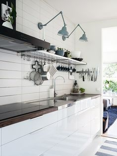 nice white #kitchen. Dusty blue accents. Stainless steel counters. efficient use of space