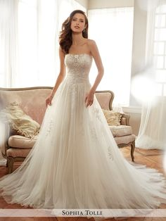 Sophia Tolli - Y11706 Harriet - Strapless tulle soft A-line gown with semi-sheer neckline, bodice generously embellished with hand-beaded lace appliqué softly flowing down finely gathered skirt over a slimmer silhouette, back corset, chapel length train. Removable spaghetti and halter straps included.Also available with back zipper trimmed with diamante buttons and loops as Y11706ZB.Sizes: 0 - 28Colors: Ivory/Magnolia, White