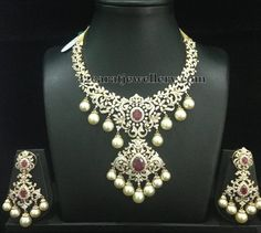Floral clasps placed huge diamond short necklace with two step designer pendant embellished in the center. Studded with round changeable r...