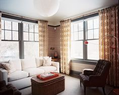 "Mod touches dot the sitting room, where a 1960s orange-and-chrome floor lamp overlooks a pair of custom tufted armchairs, and a woven storage trunk from Mecox mimics the print of the curtains. ""I don't work within a style or a period, but I'm attracted to pieces from the 30s to the 60s,"" says the designer."