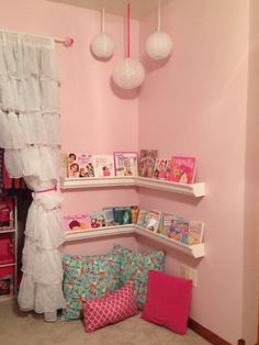 Reading corner in little girls room! We used plastic rain gutters from Lowes. Totally cheap and the the books are easy to reach and choose this way. You need to buy the long gutters and cut them to size. You'll also need end caps, and corner pieces.