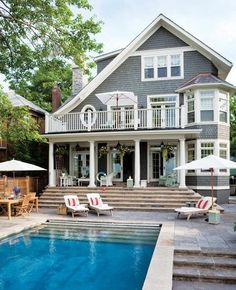 Gorgeous gray shingled home with a dreamy pool and terraced patio.