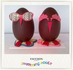FAUCHON: Retrouvez nos œufs Monsieur et Madame Swimming Poule dans notre magasin place de la Madeleine. Ces œufs d'environ 1 kg sont composés d'une coque en chocolat noir FAUCHON 67% de cacao nappée d'un mélange de chocolat au lait praliné. Ils sont décorés d'éléments en chocolat blanc et pâte d'amande de Provence.