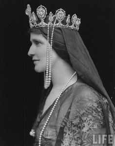 Lady Nancy Astor (nee Langhorne), wife of Viscount William Waldorf Astor, wearing elaborate headpiece composed of crown (probably set with Sancy diamond which belonged to Queen Elizabeth I) and drape of fabric and pearls.  Location:	United Kingdom  Date taken:	June 15, 1917  Photographer:	E. O. Hoppe