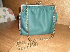 Bolso cierre de boquilla, tela étnica y combinada con verde botella,cadena para colgar.