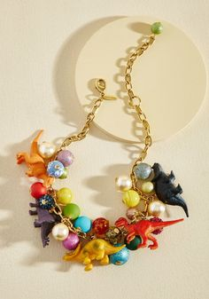 <p>Put all your energy into accessorizing with this epic necklace! A wonderfully wowing piece by Lenora Dame, this golden chain is charged up with colorful baubles, bold dino figurines, and hella personality.</p>