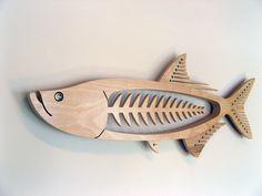Tarpon    Size 53 wide x 21 high x 2 1/4 thick. The face stands 3 1/4 from the wall. Artist Statement    Each sculpture is constructed of 3 layers of 3/4 birch plywood. I start by sketching the idea, then creating the design in a computer graphics program. After the pieces are rough cut, the layers are laminated together and shaped to their final contour. Two layers of Acrylic Varnish are applied to the surface.      Plywood often contains voids in the veneers which show up as small gaps in…