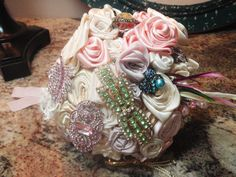 French-wrapped, this bouquet is embellished with large vintage brooches of green and pink, with one darling blue bumblebee brooch. Medium sized, six inches in diameter, adorned with pink pearls and delicate feathers of pink, purple, green, and ivory. Lavender, green, and pink-peach silk hand-rolled and stitched roses are alongside light ivory and cream premium double-faced satin hand-rolled and stitched roses. One beautiful dragonfly pink and green brooch; one large green rhinestone bow…