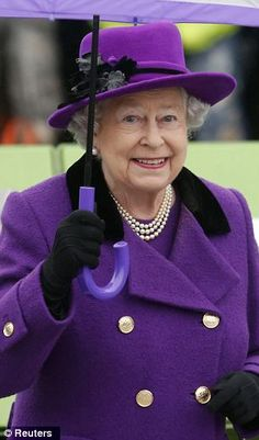 Queen Elizabeth brightens up a damp day in a stylish violet coat and trendy fedora hat on a visit to the Jubilee Gardens