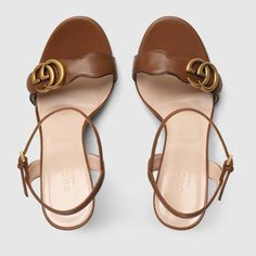 Shop the Leather Double G sandal by Gucci. An emblem of the GG Marmont line, the Double G is an archival play on the original Running G, a belt buckle that first appeared in Gucci collections in the 70s. For Pre-Fall 2018, the antique gold-toned detail enhances a pair of high-heeled brown leather sandals.