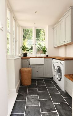 "Traditional Laundry Room with Signature Hardware 20"" Reinhard Fireclay Farmhouse Sink, slate tile floors, Built-in bookshelf"