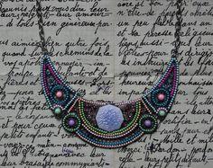 Collier fantaisie de type plastron vert/bleu/rose/jaune/violet, composé de 3 belles pièces articulées en métal argenté, rehaussées de petits cabochons, perles, céramique et strass. Au centre, 1 joli palet en céramique violette craquelé.