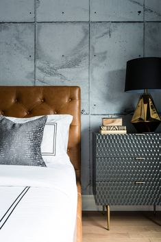 Cognac colored tufted leather headboard with white linens and dark side table with gold tone accent lamp