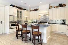 U-shaped kitchen design with white cabinets and central white island with seating for three people
