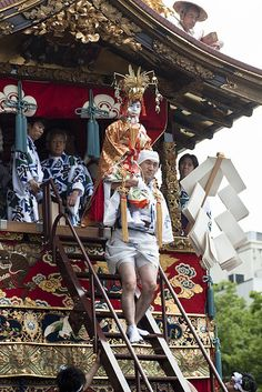 On the Naginata Hoko float is the chigo, a young boy in Shinto robes and crowned by a golden phoenix, chosen from among the Kyoto merchant families as the deity's sacred page. After weeks of special purification ceremonies, during which he lives isolated from contaminating influences such as the presence of women, he is carried atop the float as he is not permitted to touch the ground. The boy must cut a sacred rope with a single stroke to begin the Gion matsuri. Photograph by yocca on…