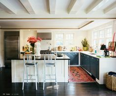 Kitchen from Lonny magazine, old turkish rug, island with black countertop, black cabinets with white counter top, open shelving