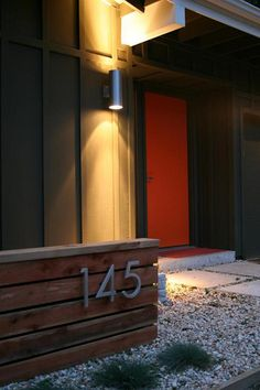 Great design idea for the front yard.  Display the house numbers on small wood fence with up lighting.
