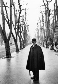 Henri Cartier-Bresson- Image represents line and shape really well as here you see the bare tree limbs form a V shape ending in a vanishing point as the background for the triangular black black shape of a man in hat and cape.
