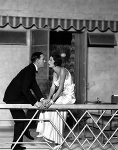 """Noel Coward (1899–1973) and Gertrude Lawrence sit on a balcony staring into each others eyes, in a scene from the play """"Private Lives"""", at the Phoenix Theatre, London, 1930. Costumes by Molyneux. (Photo by Sasha)"""