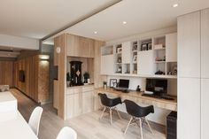 From the kitchen island, a desk area with room for two computers and plenty of storage is built into the wall from natural wood. Recessed lighting above the desk provides illumination.
