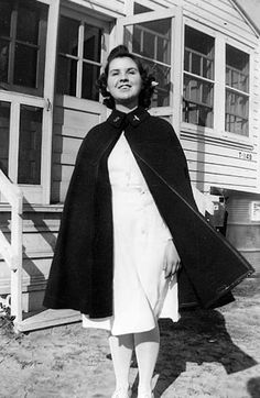Lucy Slade Libby poses in front of a building at Camp Davis, North Carolina, circa 1942. She wears the ANC blue wool cape with her Duke University nurses dress and cap ~