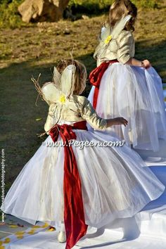 Flower girls become Christmas angels with red satin sashes and little wings