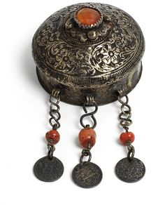 Talisman holder, made in Algeria 19th century  Silver circular talisman box / holder, with domed lid with embossed design, knop of faceted carnelian, three pendants with coral beads and coins dated AH 1299.  courtesy V Museum