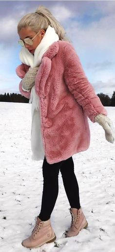 #winter #outfits  pink coat with white scarf, gray hand warmers, black fitted pants, and pink Timberland work boots