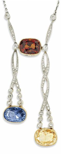 AN EDWARDIAN GEM-SET PENDANT, CIRCA 1910. The fine link chain with cushion shaped bronze coloured garnet centre, suspending two openwork millegrain-set rose-cut diamond spiralling panel links and cushion shaped yellow and blue sapphire terminal drops, weighing approximately 6.71 and 6.96 carats respectively, 46.8cm. #Edwardian #pendant