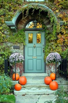 Beautiful blue front door surronded by vines and pumpkins.