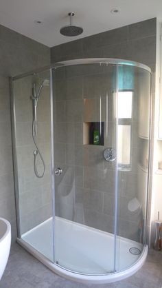 Large offset quadrant shower enclosure with rain shower, handset, large grey porcelain tiles and niche