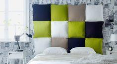 Sängynpääty, joka on tehty sinisistä, vihreistä, beigeistä ja valkoisista tyynyistä, jotka on ommeltu yhteen