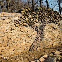 A stone wall with an incredible tree made of river rock.