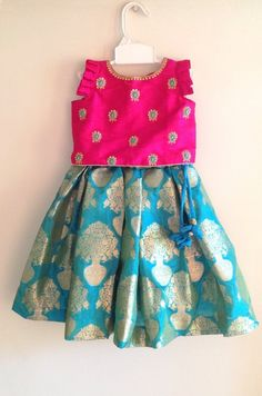 Beautiful pink silk top with a stunning hand embroidery paired with a turquoise blue brocade skirt. The top has flutter sleeves Frocks For Girls, Dresses Kids Girl, Kids Outfits, Kids Indian Wear, Kids Ethnic Wear, Baby Lehenga, Kids Lehenga, Kids Frocks Design, Baby Frocks Designs