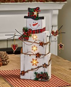 """This jolly Lighted 18"""" Country Snowman is ready to help you celebrate the season. Wrapped in fairy lights, this classic character'splaid hat and scarf are"""