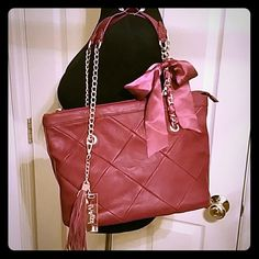 """🎉Final Sale🎉 Izzy & Ali Blake Tote Very gently used Izzy & Ali Blake satchel.  Burgundy (4th pic best depicts color)...quilted front design...logo tassel...satin ribbon woven through chain.  Double chain shoulder straps 9"""" drop.  11""""h x 16"""" w.  Bottom has protective feet.  Gold hardware...dust bag included.  Sale only. Izzy & Ali Bags Shoulder Bags"""