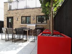 """For this Chicago backyard, Topiarius used Italian porcelain Evo pavers, which Jenkins-Sutton says can take the cold. """"They're on a sand base, similar to other patios."""" Red fiberglass containers, planted with Japanese tree lilacs, provide a pop of color. The fence was stained to match the windows and door to the owner's garage. """"The client loved this aesthetic and the concept of clean lines,"""" Jenkins-Sutton says. """"She was willing to put in a little bit of color."""""""