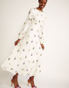 Full front view of model twirling in floral printed silk maxi dress with bell sleeves