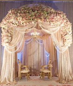 Lavish mandap! Cream fabric draped mandap with flower s. Gorgeous Chuppah.