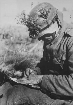 Landser (Infantry soldier) writes a letter home from the frontline. Note the use of foliage as camouflage on his stahlhelm.