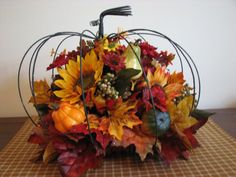 This Floral arrangement would make a rustic and beautiful addition to your fall decor. I took a wire pumpkin and added silk flowers & leaves,styrofoam gourds and pumpkins and sprigs of berries in vibrant fall hues for an arrangement that is sure to provide an impact wherever you display it. It would look beautiful on your dining table or on a hearth.  Pumpkin is 12 tall and 14 diameter.