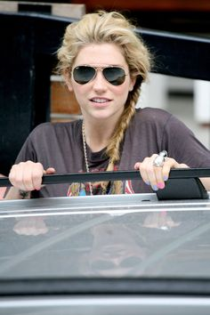 Ke$ha rocks a t-shirt, Ray Ban sunglasses, a necklace, and a braid.
