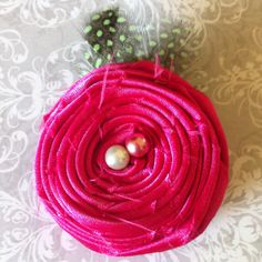 Rolled satin flower w/pearly bead & feather accents. This is a clip that can be worn on a headband or by itself. For any age!