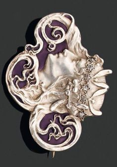 An Art Nouveau brooch by René Lalique. An oval brooch representing a profile of a woman wearing a coronet of mistletoe set with rose-cut diamonds, on a purple enamel background. Mounted in gold and silver. Signed. #ArtNouveau #Lalique #brooch