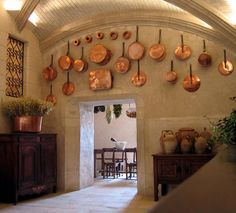 this French country kitchen features hanging cookware, stone construction and stucco walls