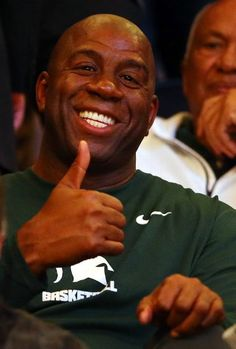 """Earvin """"Magic"""" Johnson gives the thumbs up during the regional semifinal of the 2014 NCAA Men's Basketball Tournament between the Michigan State Spartans and the Virginia Cavaliers at Madison Square Garden on March 28, 2014 in New York City. (Photo by Elsa/Getty Images)"""